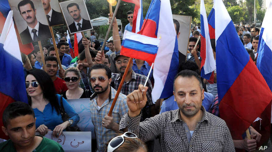 This photo from the Syrian official news agency SANA shows Syrians rallying in front of the Russian Embassy in Damascus to show their thanks to Russia for its intervention in Syria, Oct. 13, 2015, but few Syrians who leave their country are finding R...
