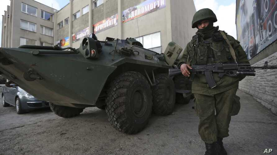A soldier in an unmarked uniform stands guard at APC outside the Ukrainian Military Prosecutor's Office in Simferopol, Crimea, Mar. 20, 2014.
