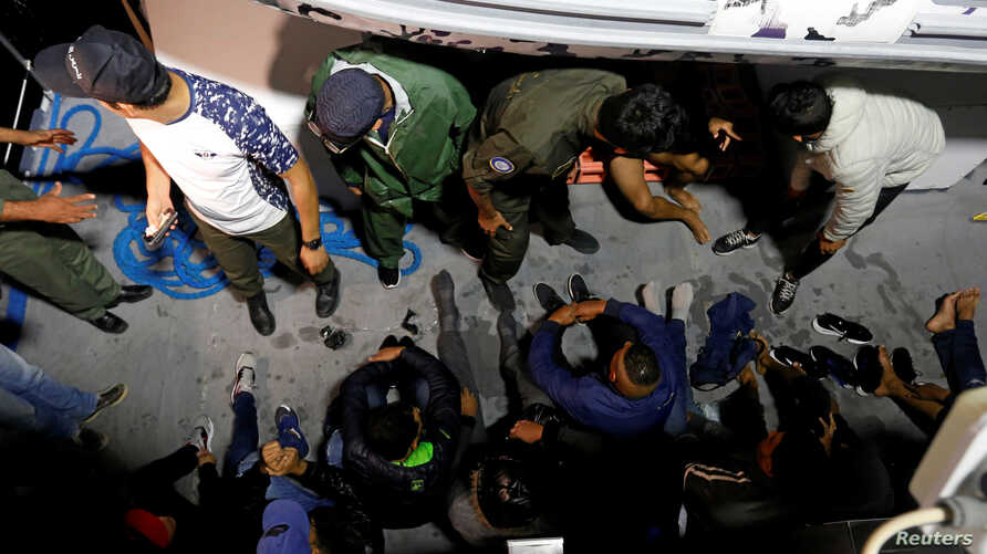 FILE - Migrants are seen on a boat after being rescued by Tunisian coast guard, off the coast of Bizerte, Tunisia, Oct. 12, 2017.