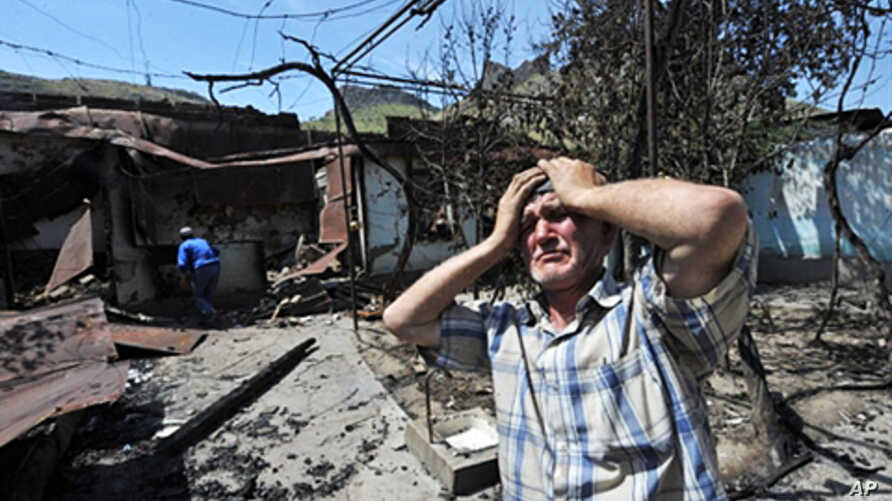 An ethnic Uzbek holds his head in his hands as he stands beside the wreckage of his burned out home in Osh, 14 June 2010
