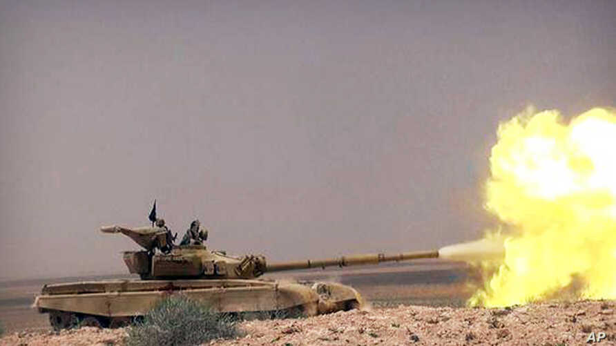 This picture released on May 20, 2015 by the website of Islamic State militants, shows a tank with Islamic State group fighters clashing with Syrian government forces on a road between Homs and Palmyra, Syria.