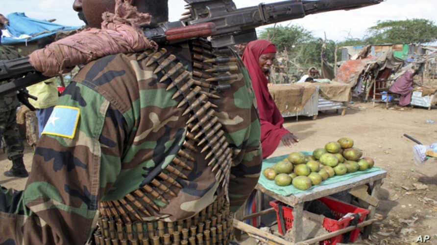 A fruit seller looks across as a Somali government soldier stands guard in Afgoye, west of the capital Mogadishu, in Somalia on June 7. A recent survey conducted by VOA's Somali Service reveals widespread agreement on many key provisions of the draft