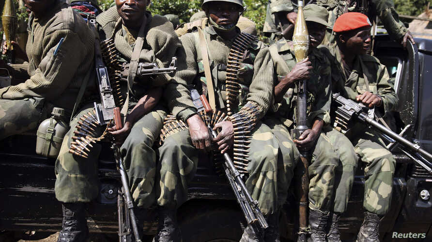 Congolese army (FARDC) soldiers sit in a military truck in Minova, some 45 km (28 miles) west of Goma, November 26, 2012.
