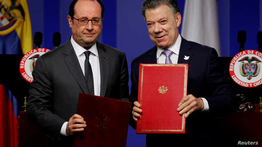 France's President Francois Hollande (L) and his Colombian counterpart Juan Manuel Santos pose for photographs with signed agreements during a joint news conference at the presidential palace in Bogota, Colombia, Jan. 23, 2017.