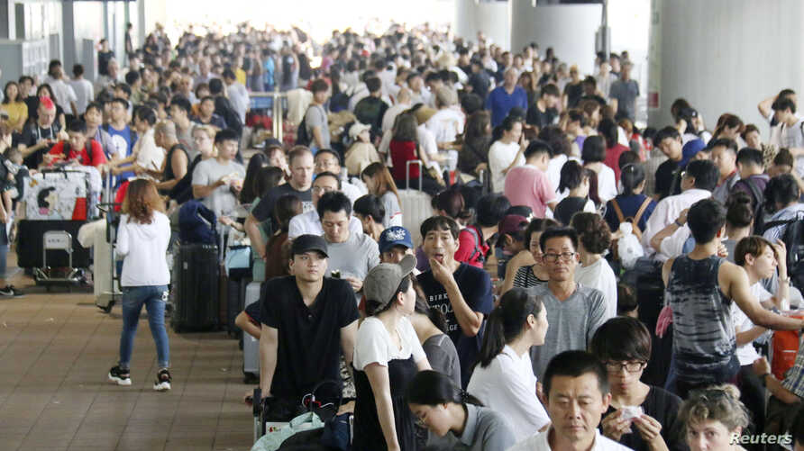 Passengers stranded at Kansai International Airport by Typhoon Jebi line up outside the airport as they wait for the arrival of a special bus service to transport them out of the area, in Izumisato, Japan, Sept. 5, 2018.