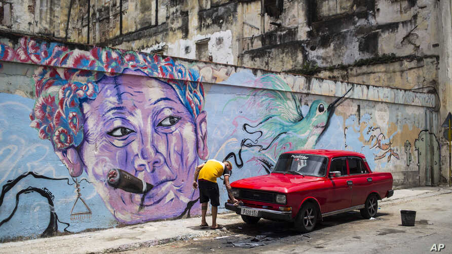 FILE -  A man washes a car next to a mural of a woman smoking a cigar, in Havana, Cuba,  Aug. 9, 2018. The country is softening a heavily criticized new law known as Decree 349 that would have created a corps of powerful art inspectors able to shut d