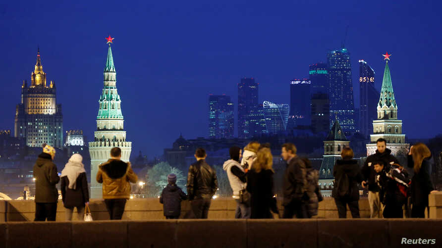 FILE - People stand on the Great Moskvoretsky Bridge, with the headquarters of Russian Foreign Ministry seen in the background, in central Moscow, Russia, March 28, 2016.