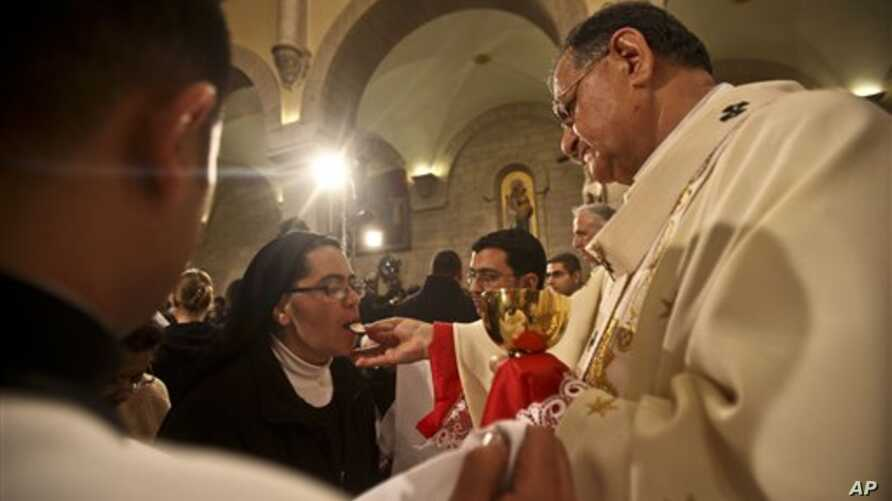 A nun takes communion from Latin Patriarch of Jerusalem Fouad Twal during Christmas midnight mass at the Church of the Nativity, traditionally believed to be the birthplace of Jesus Christ, in the West Bank town of Bethlehem early Saturday, Dec. 25,