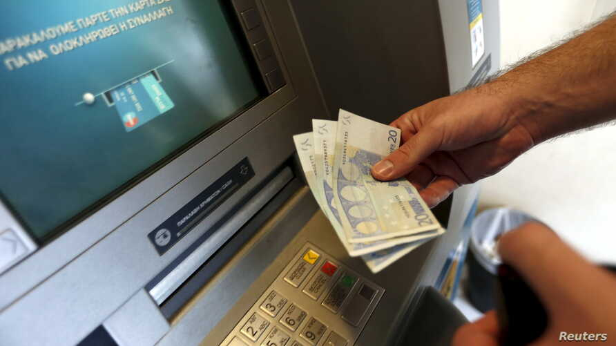 A man withdraws sixty Euros, the maximum amount allowed after the imposed capital controls in Greek banks, at a National Bank of Greece ATM in Piraeus port near Athens, Greece, June 30, 2015.