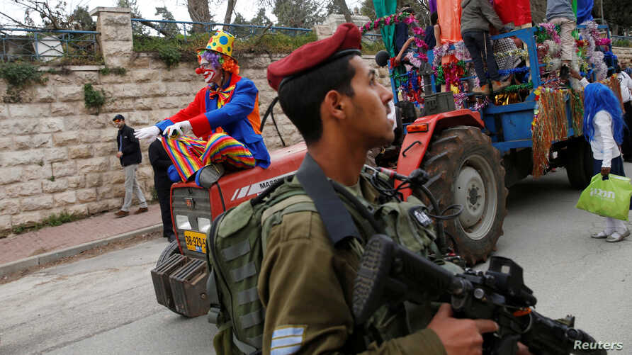 An Israeli soldier secures a parade marking the Jewish holiday of Purim in the West Bank city of Hebron, March 12, 2017.