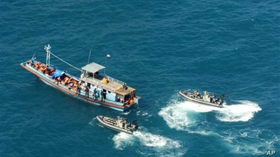 In this image provided by the Department of Home Affairs, two launches, right, from HMAS Launceston, not seen, intercept a boat, believed to be carrying 72 suspected asylum seekers,  near Bathurst Island, in the Arafura Sea north of the Northern Terr