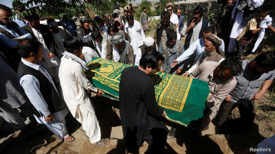 FILE - Afghans take part in a burial ceremony of Afghan journalist Zabihullah Tamanna, in Kabul, Afghanistan, June 7, 2016.