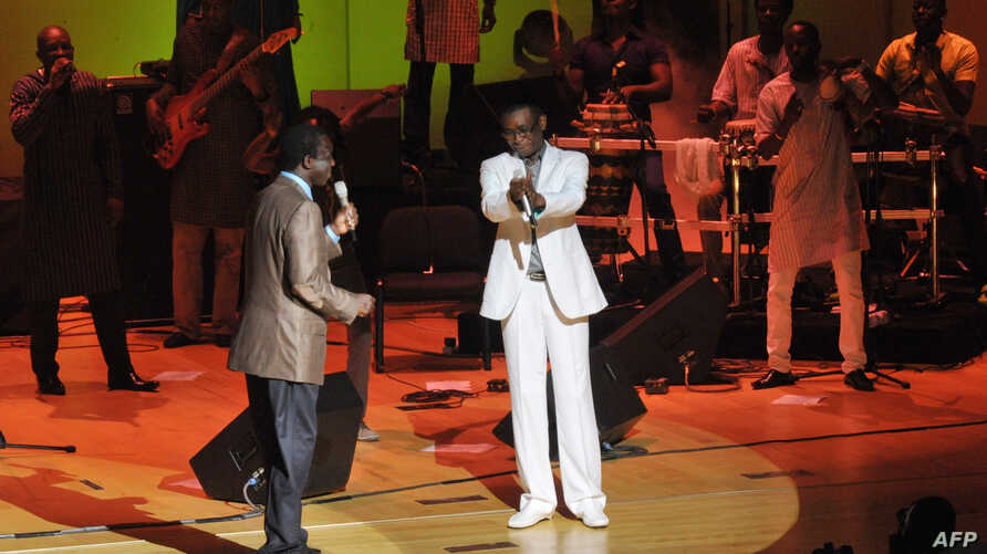 Senegalese singer and Culture Minister Youssou Ndour (C) and Senegalese singer Thione Seck (L) perform at a relief concert for flood victims at Dakar's Grand Theater on September 8, 2012.
