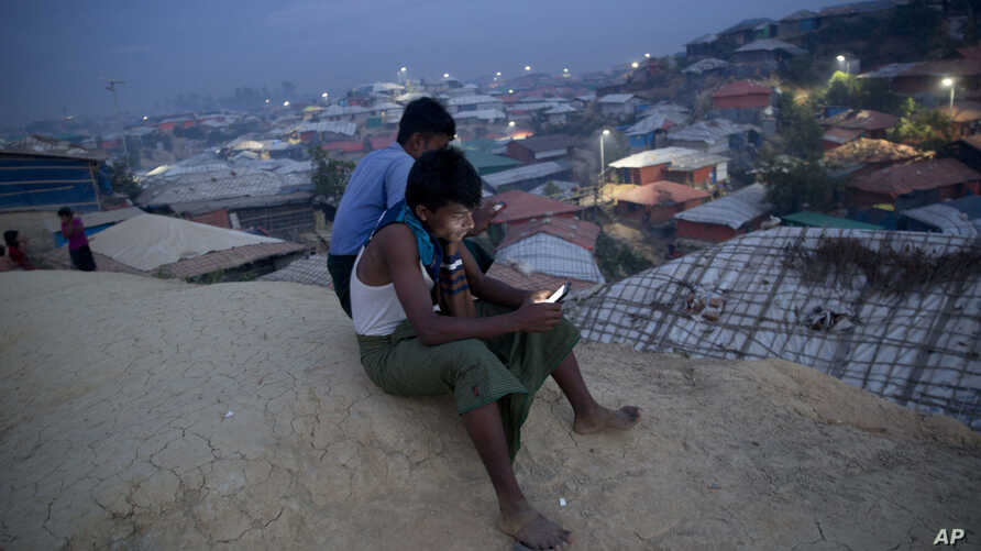 Rohingya Muslims use their cellphones as they sit on a hillock overlooking Balukhali refugee camp, in Bangladesh, Nov. 14, 2018. Bangladesh authorities said they are ready to begin repatriating some of the more than 700,000 Rohingya Muslims who have