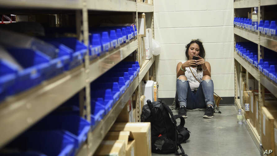 A young woman checks her phone while hiding inside the Sands Corporation plane hangar after a mass shooting in which dozens were killed at the Route 91 Harvest Festival on Oct. 1, 2017, in Las Vegas.