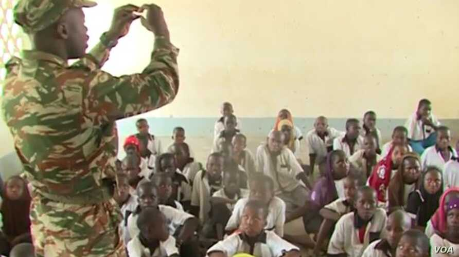 A Cameroonian soldier teaches children at a government school in Fotokol, May 11, 2018. (M. Kindzeka/VOA)