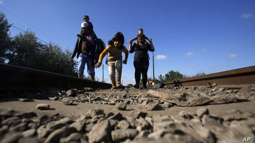 Migrants cross the border line between Serbia and Hungary near Roszke, southern Hungary, Sept. 8, 2015.