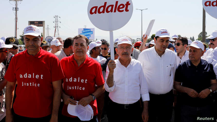 """FILE - Turkey's main opposition Republican People's Party (CHP) leader Kemal Kilicdaroglu (C) and Secretay General of the Socialist International Luis Ayala (2nd L) walk flanked by supporters during the 14th day of a protest dubbed """"justice march"""" ag"""