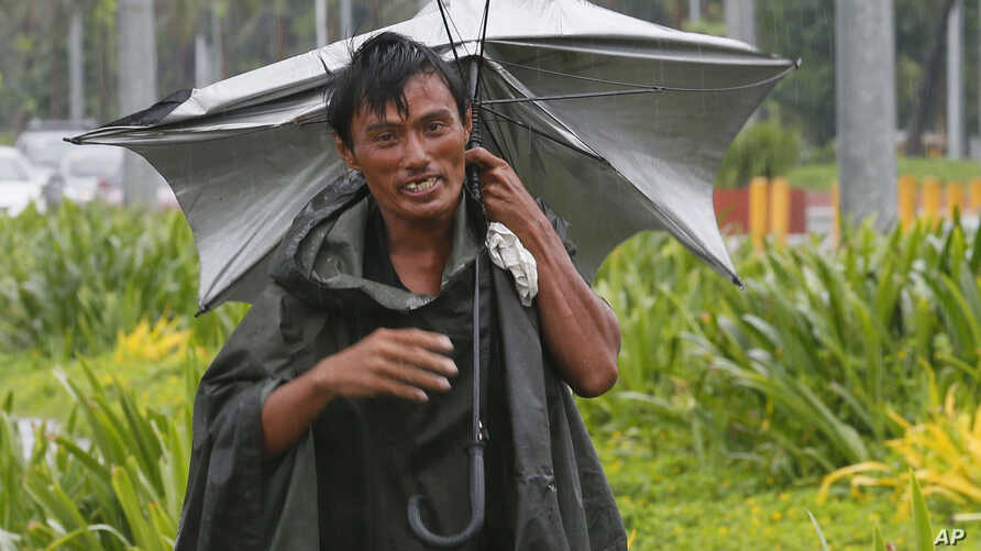 A man walks along a boulevard under the slight rain in Manila, Philippines, Oct. 16, 2016. Typhoon Sarika, with sustained winds of 130 kilometers (80) miles per hour and gusts of 220 kph (136mph), has slammed into the northeastern Philippines.