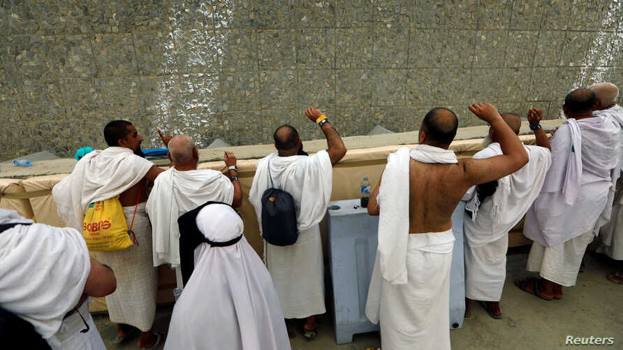 Muslim pilgrims cast stones at a pillar that symbolizes Satan, during the annual haj pilgrimage in Mena, Saudi Arabia, Aug. 21, 2018.