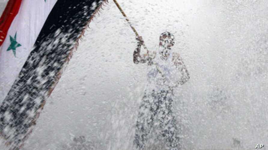 A pro-Syrian regime protester, waves a Syrian flag from a fountain during a demonstration in Damascus, Syria, November 16, 2011.