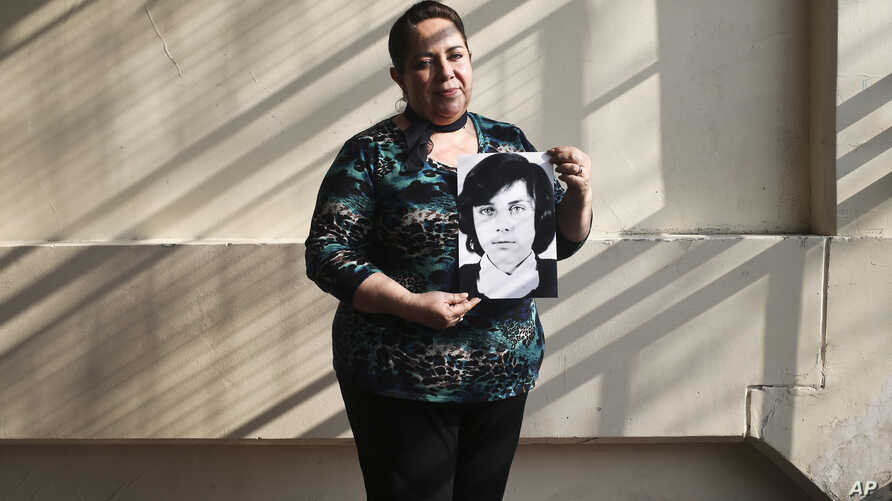 In this  Sept. 6, 2018 photo, 54-year-old teacher Vittoria E Natto poses for a portrait inside her high school holding a photo of herself when she was 9 years old, in Santiago, Chile.