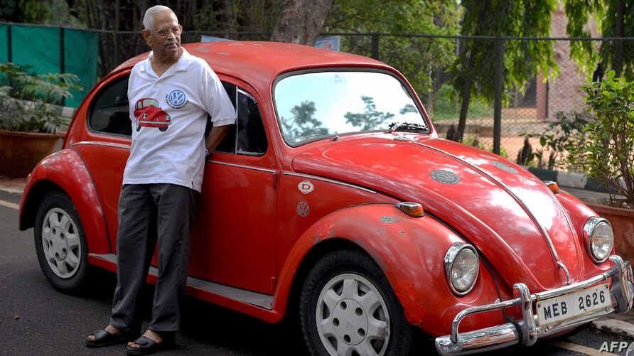 """FILE - A Volkswagen car enthusiast stands next to a vintage Volkswagen Beetle car during a rally held as part of the 23rd anniversary of """"World Wide VW Beetle Day,"""" in Bangalore, India, on June 24, 2018."""
