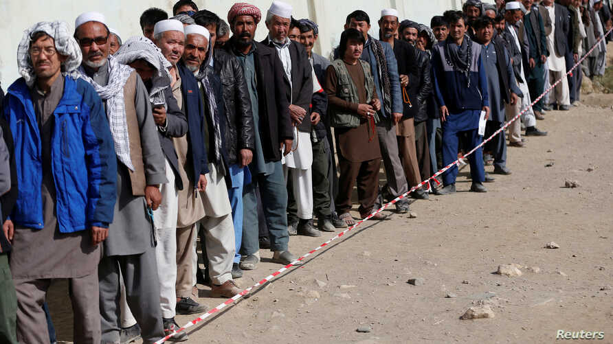 FILE - Afghan men line up to cast their votes during the parliamentary election at a polling station in Kabul, Afghanistan, Oct. 21, 2018.