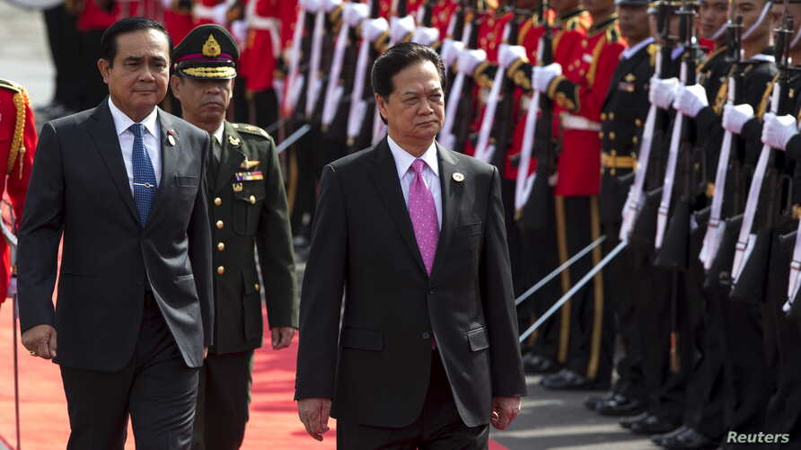 Vietnam's Prime Minister Nguyen Tan Dung, center, and Thailand's Prime Minister Prayuth Chan-ocha review the honor guard during a welcoming ceremony at Government House in Bangkok, Thailand, July 23, 2015.