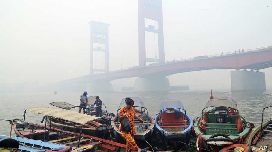 FILE - A woman disembarks from a boat with the Ampera Bridge shrouded in haze from wildfires in Palembang, South Sumatra, Indonesia, Sept. 29, 2015.