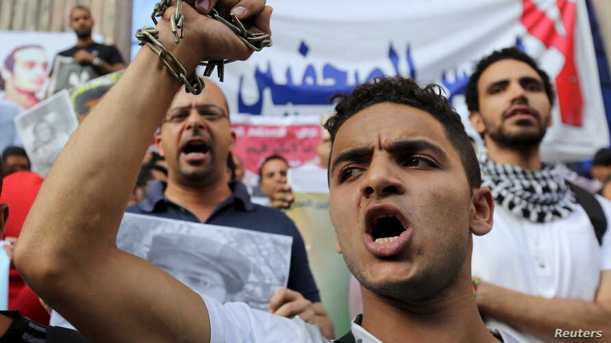 Journalists and members of the April 6 movement protest against the restriction of press freedom and demand the release of detained journalists in front of the Press Syndicate in Cairo, June 10, 2015.