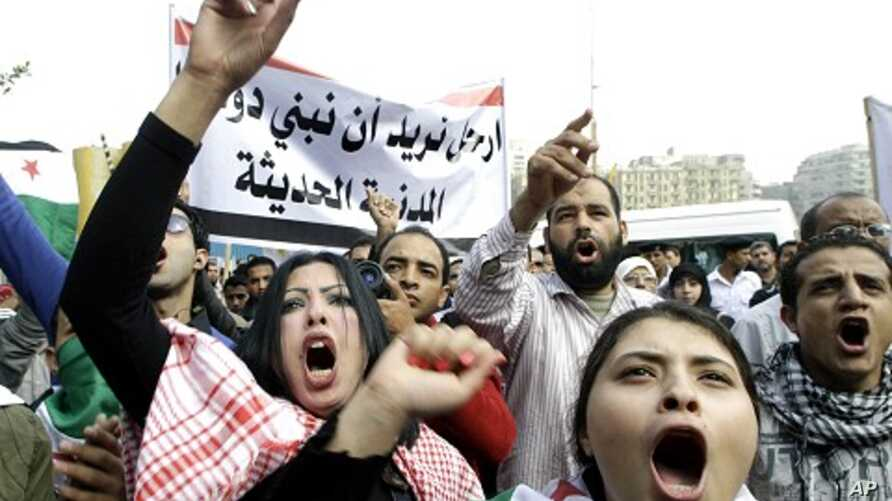 Syrian protesters shout anti-Assad slogans during a protest in front of the Arab League headquarters in Cairo, Egypt,  November 12, 2011.