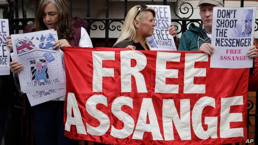 Supporters of WikiLeaks founder Julian Assange stand outside of the Ecuadorian embassy as Assange addresses the media, in London, May 19, 2017.