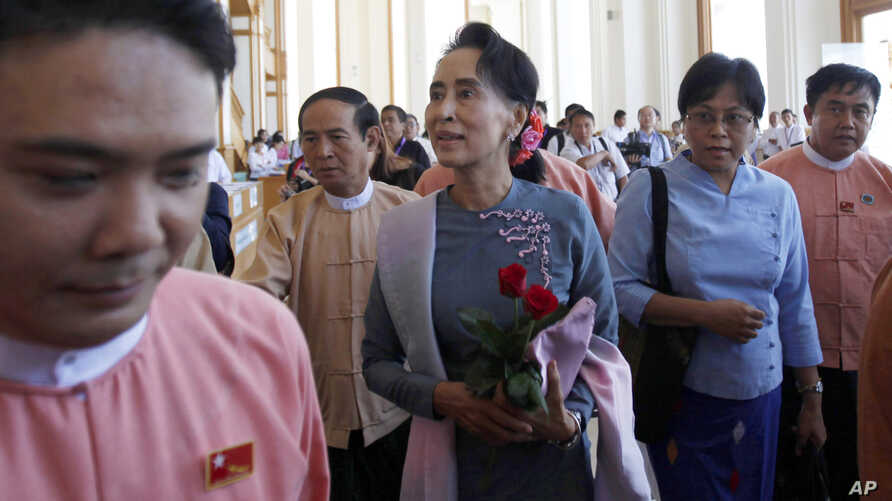 Myanmar opposition leader Aung San Suu Kyi, center, walks upon arrival to attend a regular session of lower house at parliament Monday, Nov. 16, 2015.