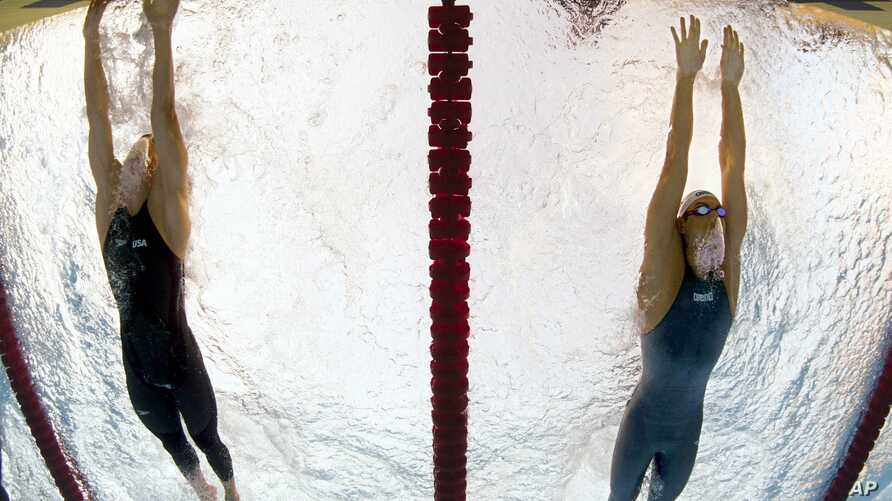 FILE - Michael Phelps of the United States, left, outsprints Serbia's Milorad Cavic to win the men's 100-meter butterfly final at the FINA Swimming World Championships in Rome, Aug. 1, 2009. Rubberized suits made a mockery of the record book at the 2