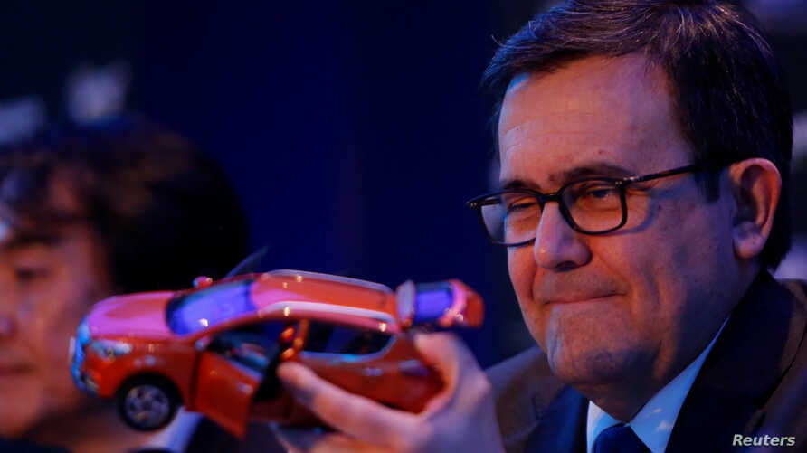 Mexico's Economy Minister Ildefonso Guajardo holds the model of a car during a news conference to announce the new plant of JAC Motors in Mexico City, Feb. 1, 2017.