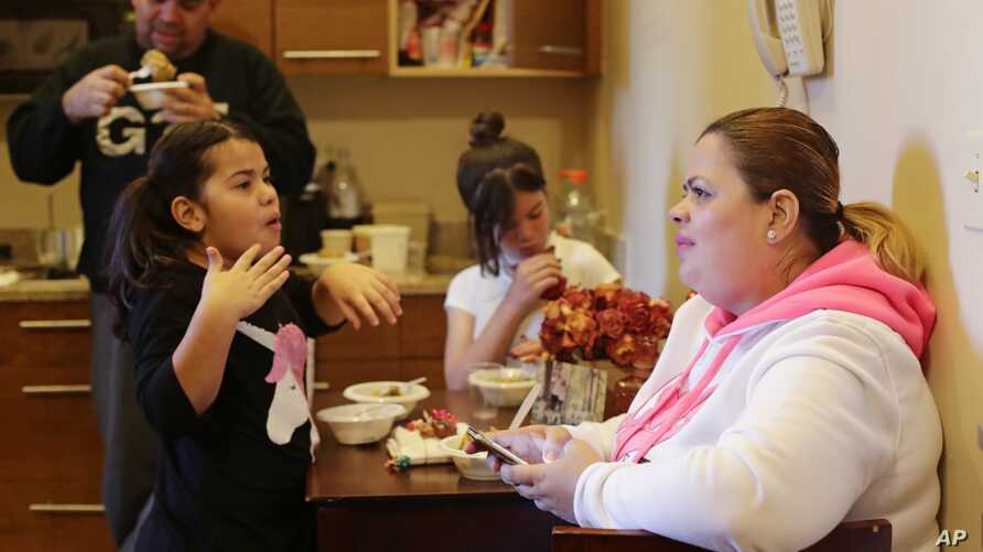 In this Jan. 9, 2018 photo, Enghie Melendez sits with her daughters Lidia, left, Alondra, and husband Fernando Moyet in their hotel kitchen in the Brooklyn borough of New York.
