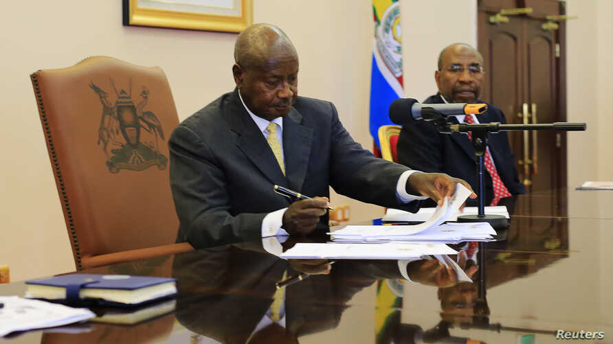 Uganda President Yoweri Museveni signs an anti-homosexual bill into law at the state house in Entebbe, 36 km (22 miles) south west of capital Kampala February 24, 2014. Museveni signed into law on Monday an anti-gay bill that toughens already strict