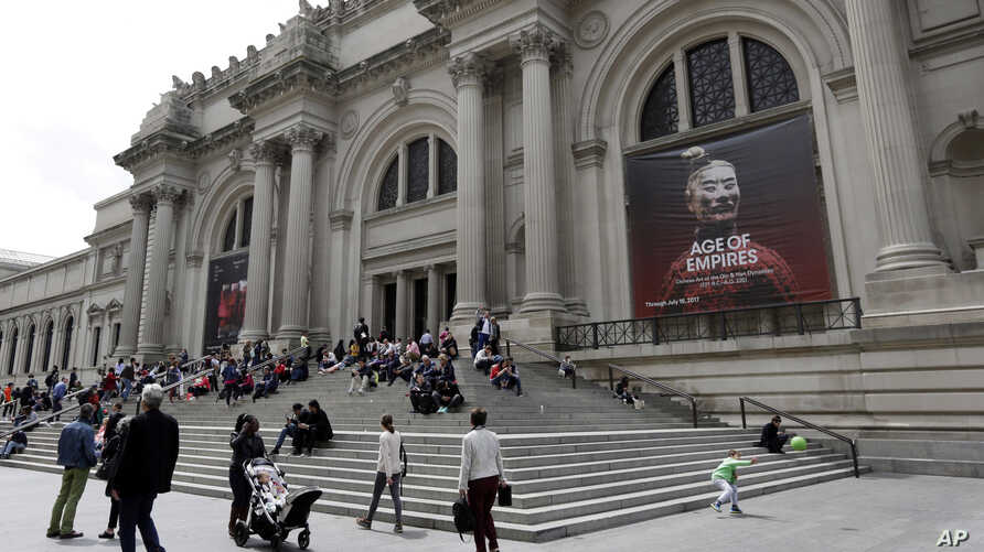 People sit on the steps at the Fifth Avenue entrance to the Metropolitan Museum of Art in New York, May 10, 2017.