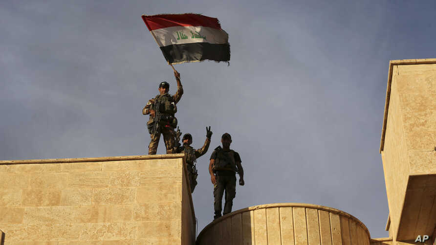 Iraq's elite counterterrorism force soldiers raise an Iraqi flag over the main church in Bartella, Iraq, Friday, Oct. 21, 2016.