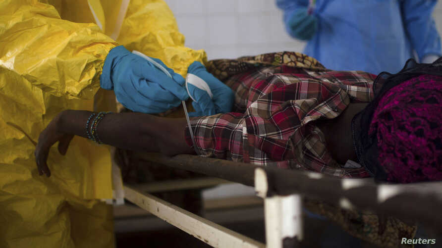 Medical staff take a blood sample from a suspected Ebola patient at the government hospital in Kenema, July 10, 2014. Ebola has killed more than 1,000 people across Guinea, Liberia and Sierra Leone since an outbreak began in February REUTERS/Tommy Tr