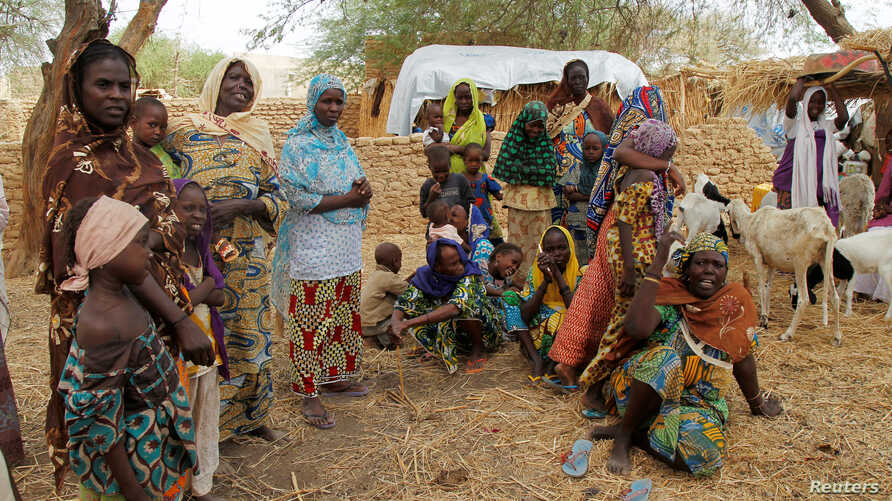 Nigerian refugees, who fled from their village into Niger following Boko Haram attacks, stand in the yard of their Nigerien host in Diffa in southeastern Niger, June 21, 2016.