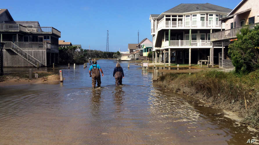 A couple walk along a road flooded with sea water brought by Hurricane Maria in Buxton, N. C., Sept. 27, 2017. Maria has weakened to a tropical storm and is headed east, northeast away from North Carolina.