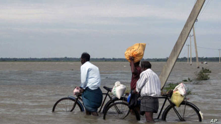 Sri Lankan men push their bicycles through flood waters after heavy rains in Batticaloa, about 320 km (199 miles) east of Colombo, 13 Jan 2011