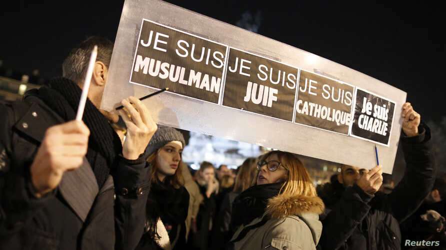 """People hold a placard which reads """"I am Muslim, I am Jewish, I am Catholic, I am Charlie"""" at a vigil, following the shooting of 12 people at the satirical newspaper Charlie Hebdo, at the Place de la Republic in Paris, Jan. 8, 2015."""