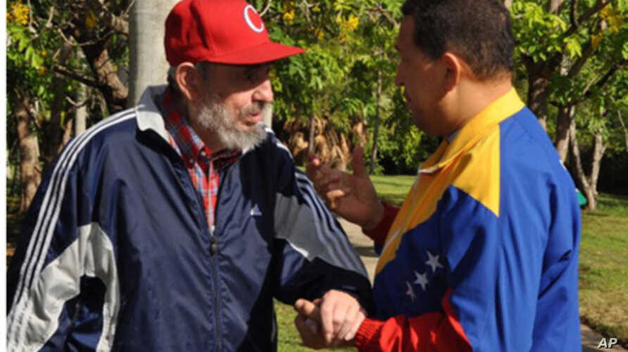 Former Cuban leader Fidel Castro and Venezuela's President Hugo Chavez (R) speak in Havana in this June 28, 2011 handout photo. Supporters of Chavez hailed the release of new footage of the socialist leader as evidence he was recovering from surgery