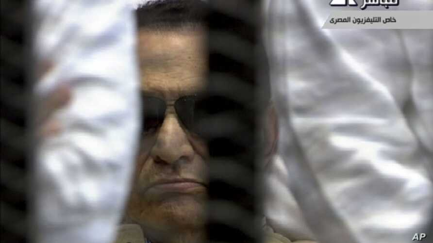 In this video image taken from Egyptian State Television, 84-year-old former Egyptian president Hosni Mubarak is seen in the defendant's cage as a judge reads the verdict in on charges of complicity in the killing of protesters during last year's upr