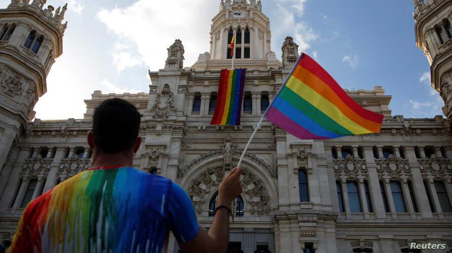 A man waves a flag as a giant rainbow flag hangs over the facade of city hall in Madrid, Spain, June 26, 2017.