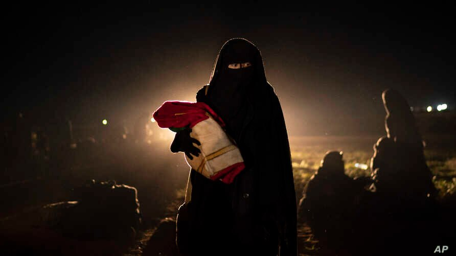 A woman who was evacuated out of the last territory held by Islamic State militants holds her baby after being screened by U.S.-backed Syrian Democratic Forces in the desert outside Baghuz, Syria, Feb. 25, 2019.