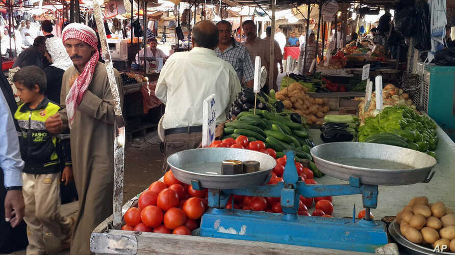 FILE - People shop at a market in the northern city of Mosul, Iraq.